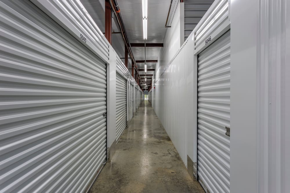 Well lit hallway of indoor storage units Space Shop Self Storage in Cary, North Carolina