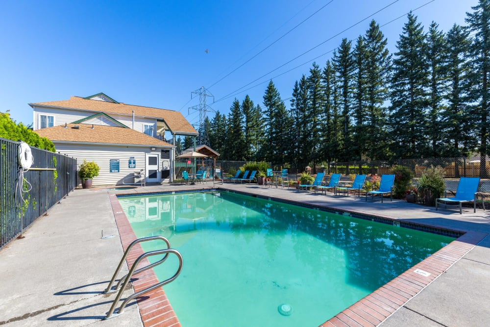 Beautiful resort-style swimming pool with lounge chairs at The Landings at Morrison Apartments in Gresham, Oregon