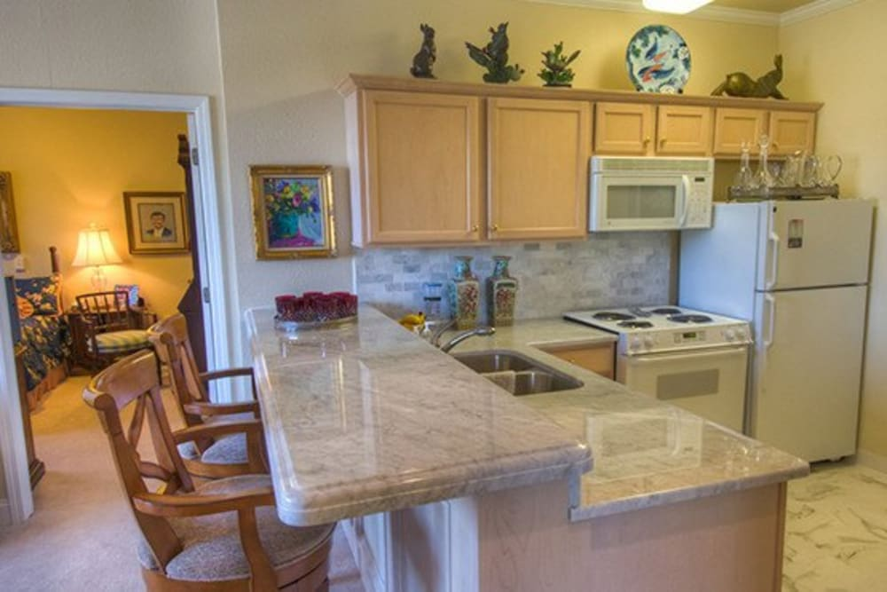 Kitchen with bar seating in senior living apartment at Mansion at Waterford Assisted Living in Oklahoma City, Oklahoma