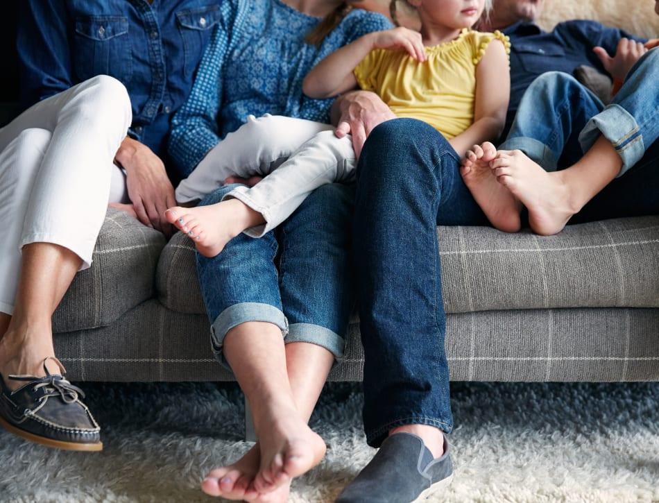Happy family's feet on the couch in their new home at Veranda La Mesa in La Mesa, California