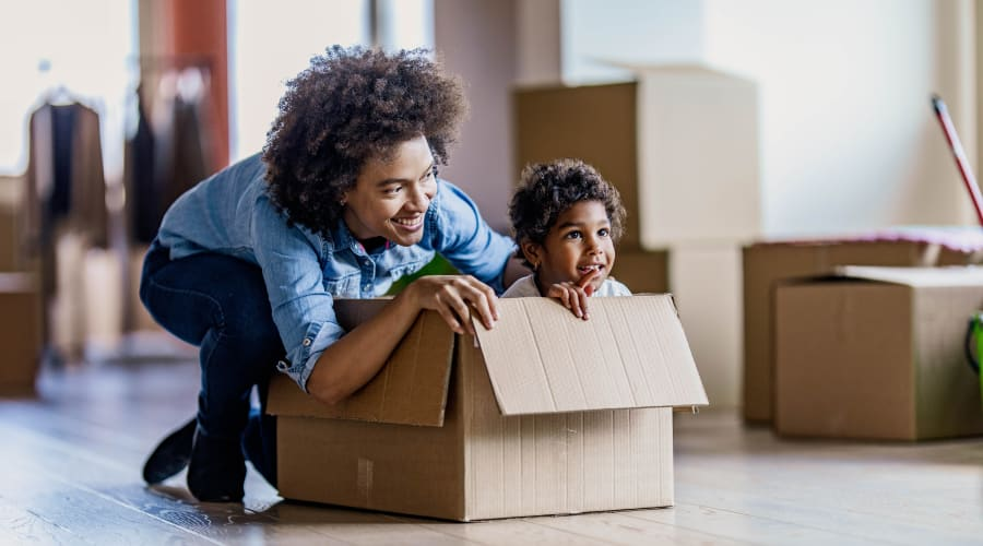 A parent pushing their child in a box at their home near KO Storage of Weatherford - West Park in Weatherford, Texas