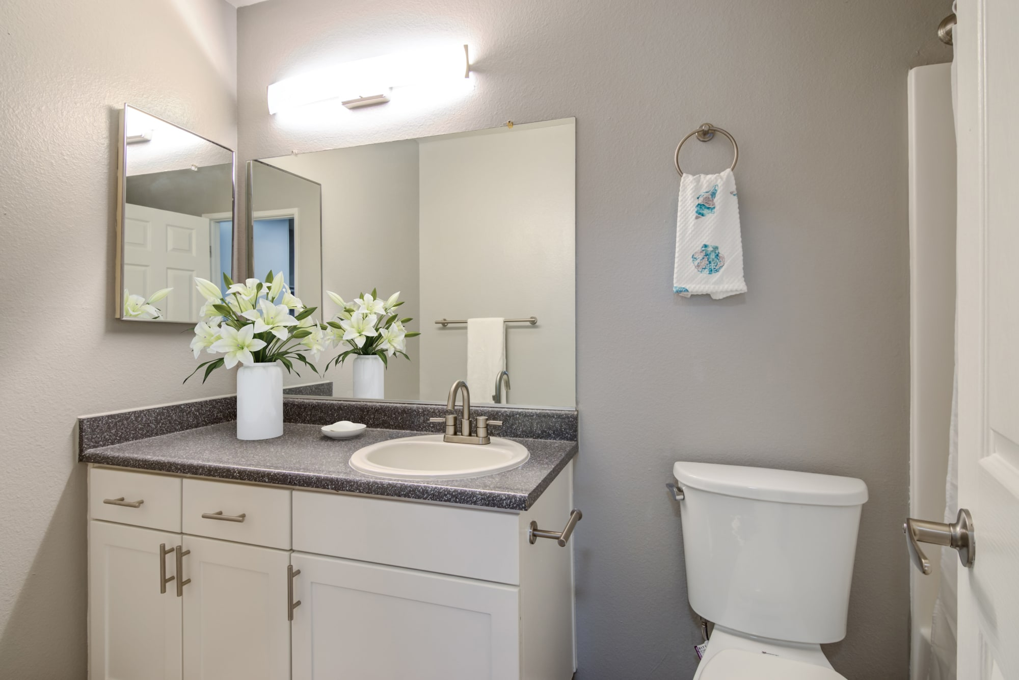A renovated bathroom with white cabinets at Hillside Terrace Apartments in Lemon Grove, California