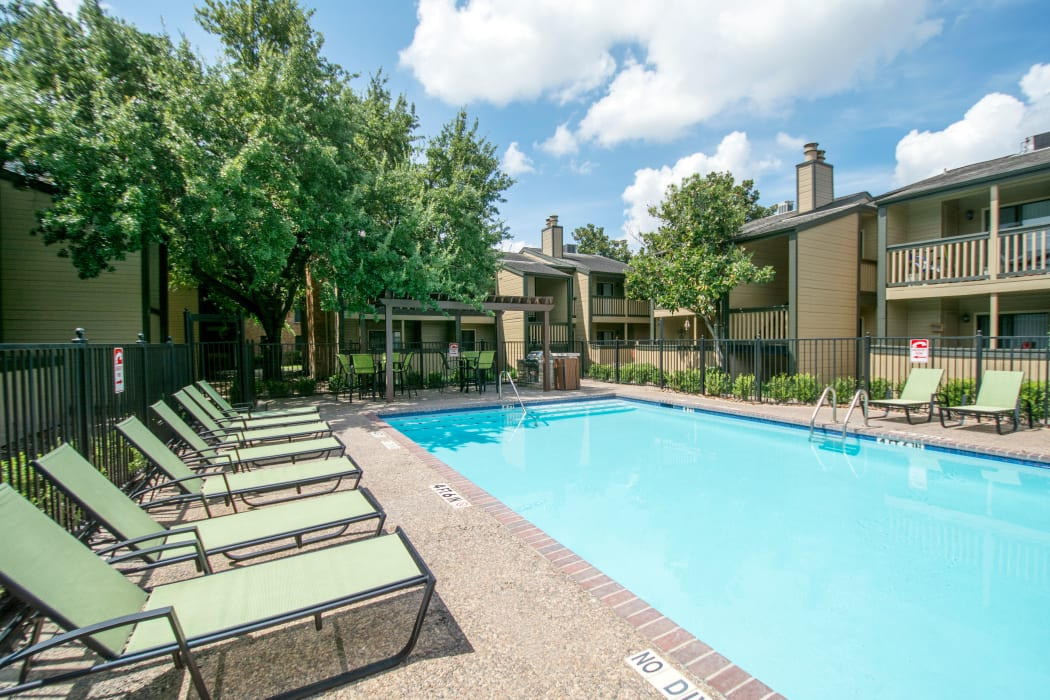 Swimming pool with lounge chairs at Stonecrossing of Westchase in Houston, Texas