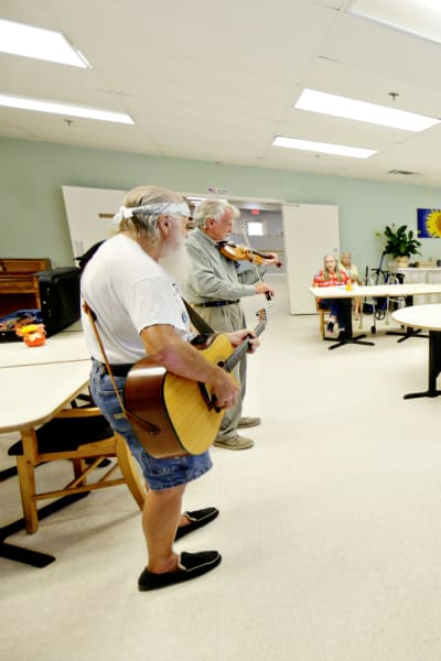 Two residents playing guitar for other residents at Providence Assisted Living in Cleveland, Mississippi