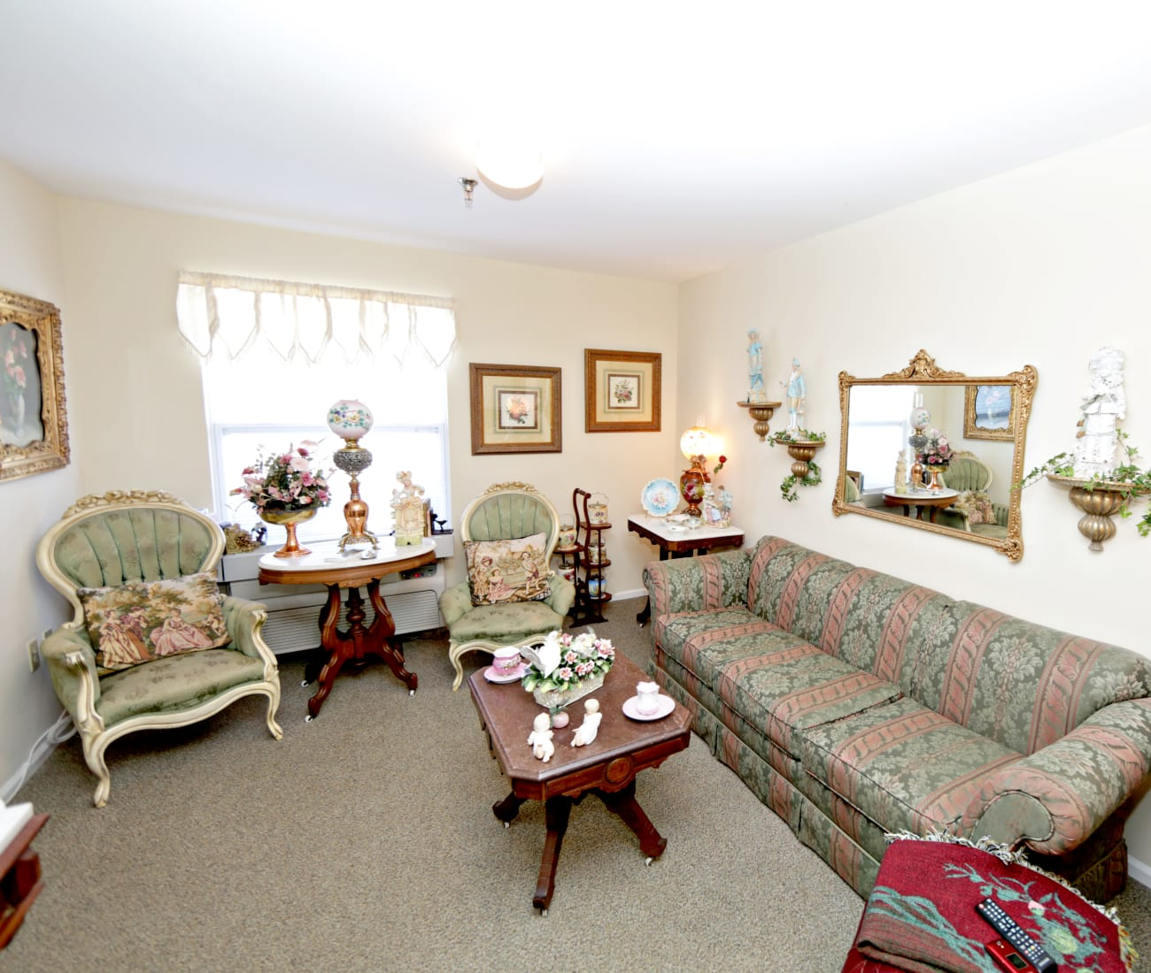 Resident living room with carpet and natural light at Providence Assisted Living in Senatobia, Mississippi