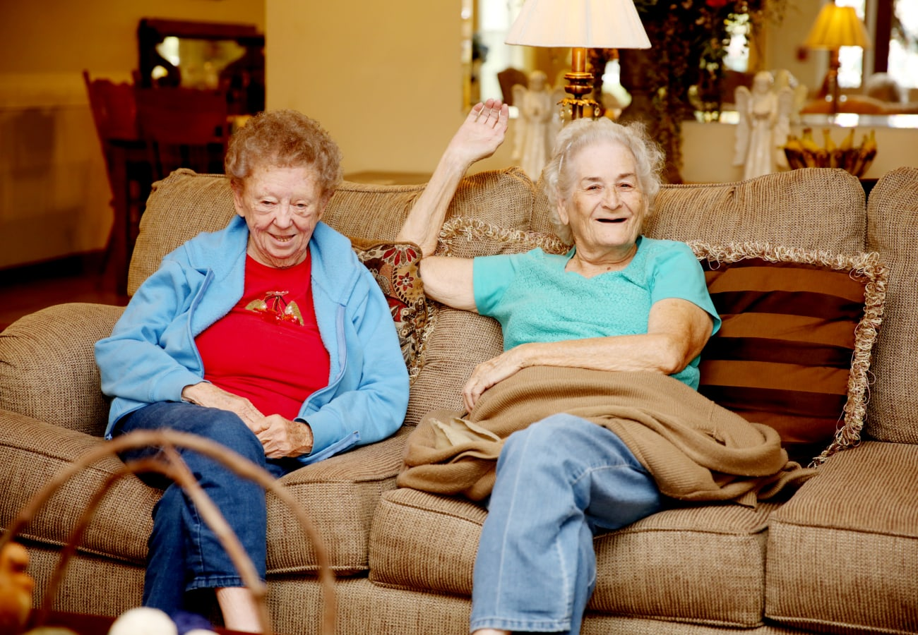Two resident friends relaxing on a couch at Providence Assisted Living in Grenada, Mississippi