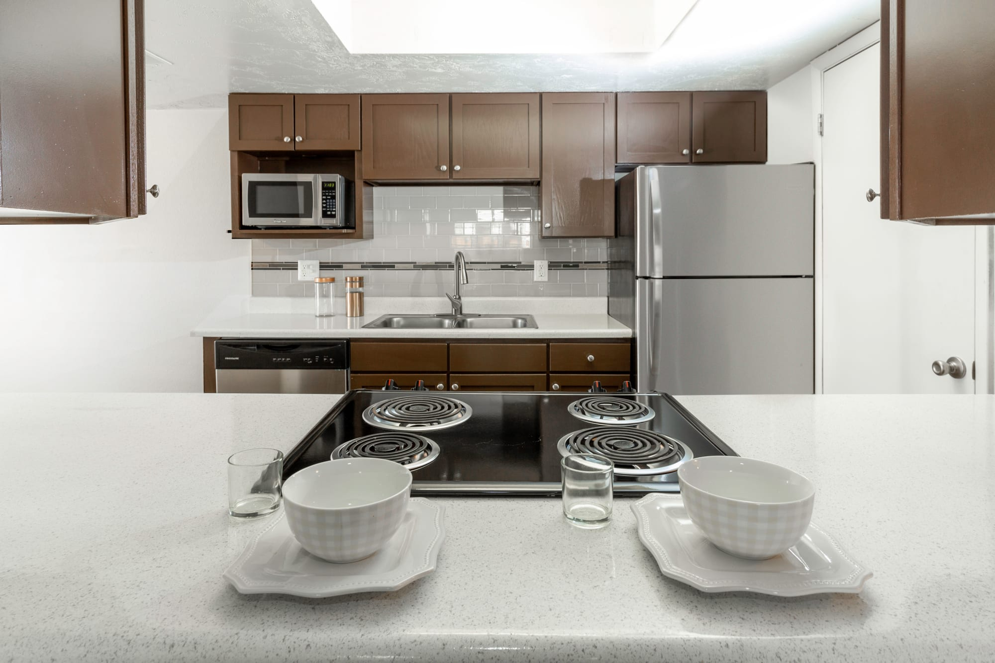 Renovated kitchen with brown cabinets at Windgate Apartments in Bountiful, Utah