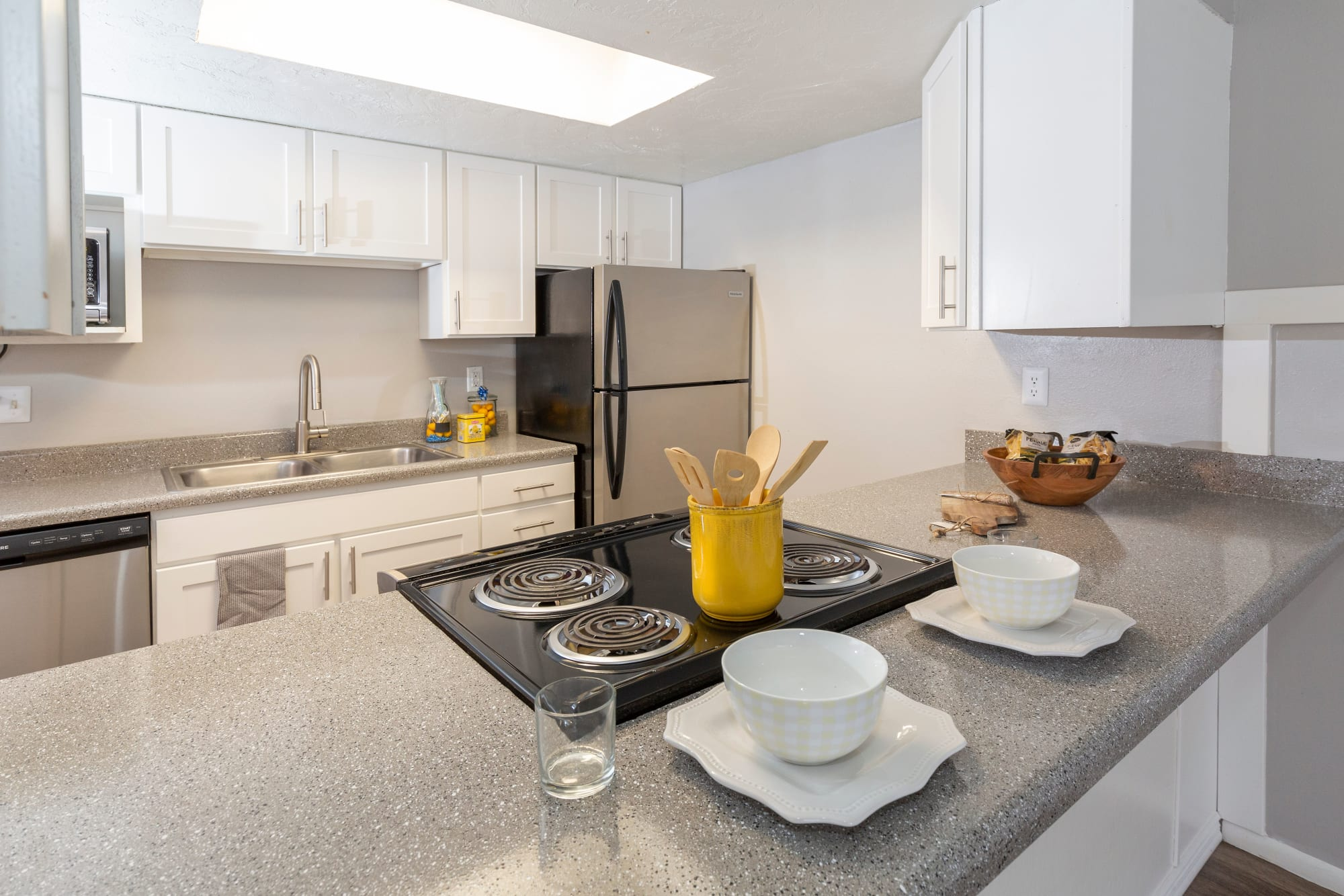 Renovated kitchen with white cabinets at Windgate Apartments in Bountiful, Utah