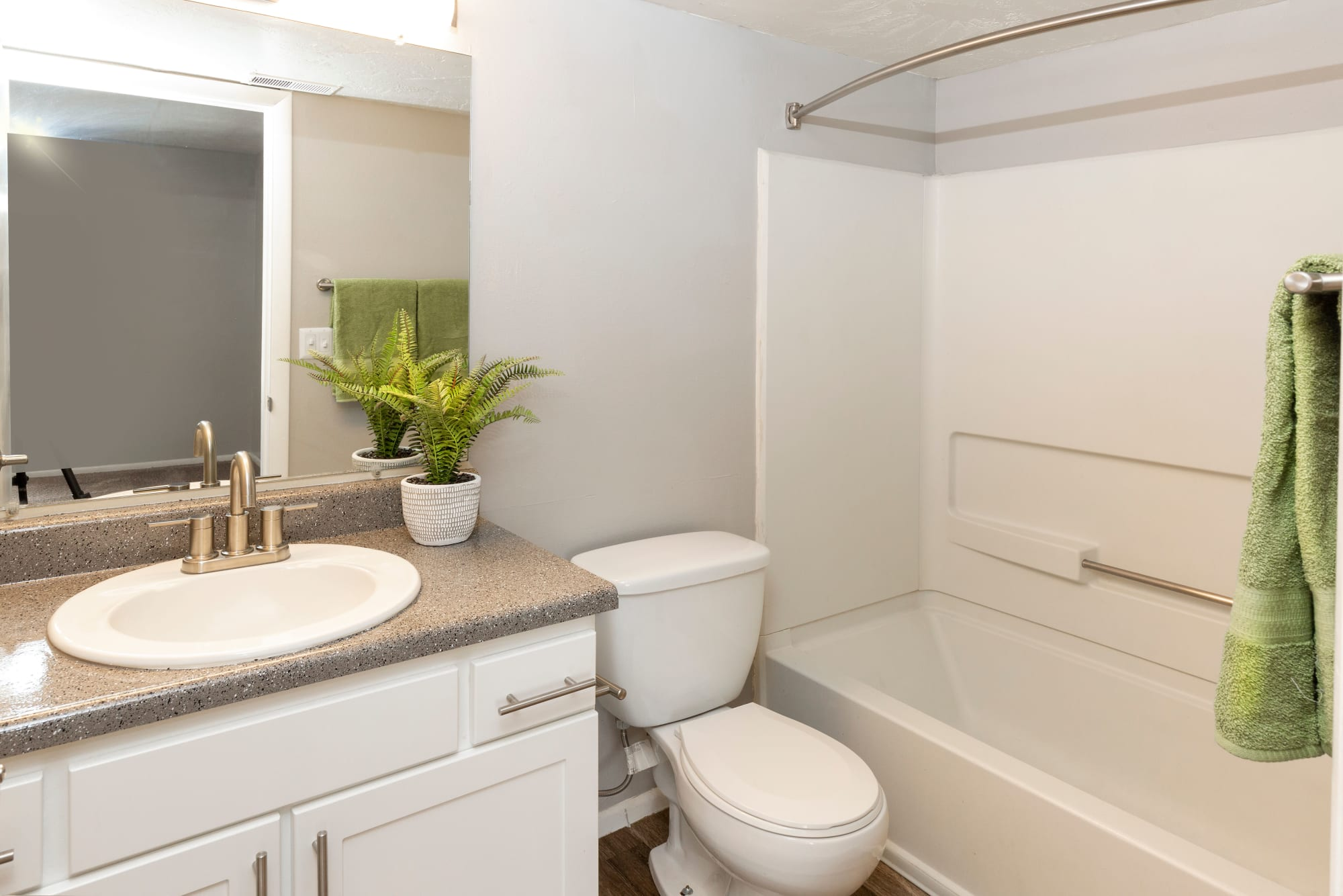 Renovated bathroom with white cabinets and a tub at Windgate Apartments in Bountiful, Utah