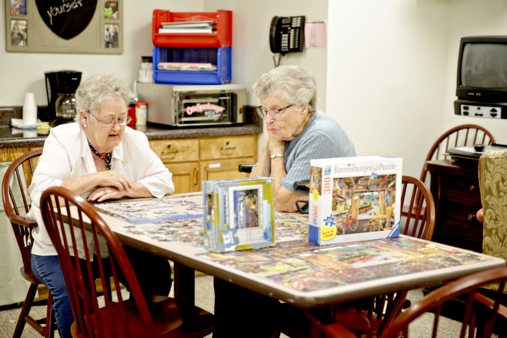 Two residents putting together a puzzle at Providence Assisted Living in Searcy, Arkansas.