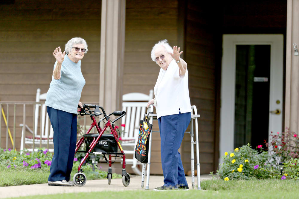 Two residents waving hello on their walk at Providence Assisted Living in Searcy, Arkansas.