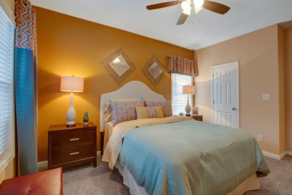 Well decorated bedroom showcasing a bright yellow accent wall at Avia at North Springs in Atlanta, Georgia