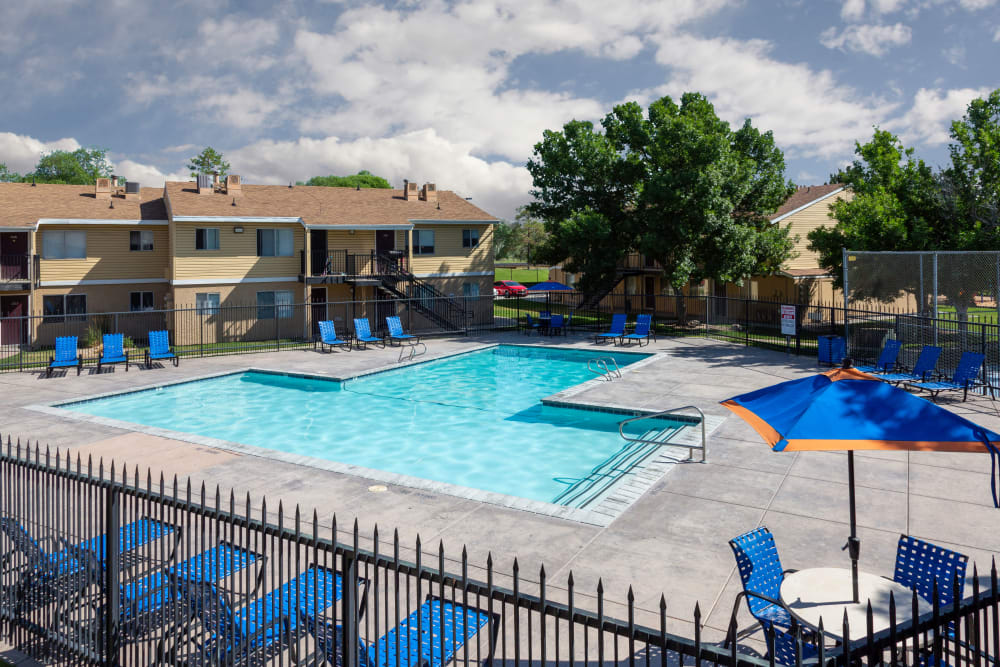 Beautiful resort-style swimming pool with a lush backdrop at Callaway Apartments in Taylorsville, Utah
