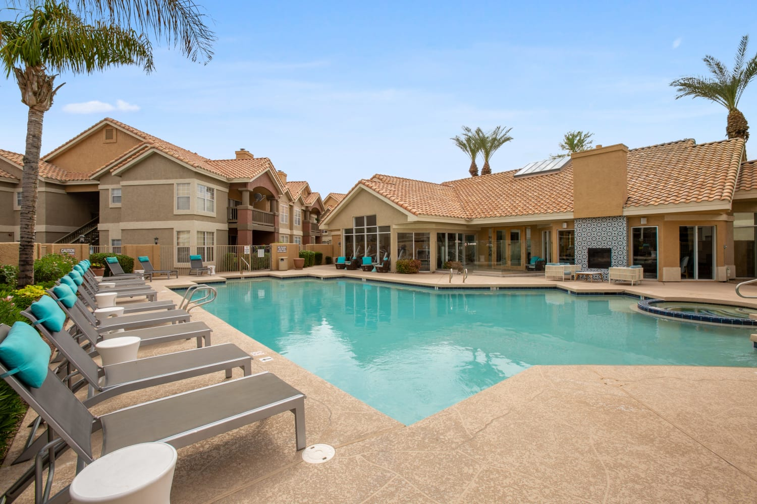 View of the pool with tanning chairs at Sonoran Vista Apartments in Scottsdale, Arizona