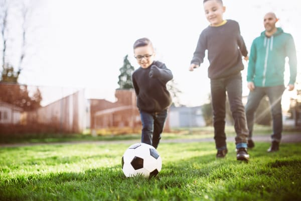 Kids playing football at Maple Trail Apartments & Townhomes in Pasadena, Texas
