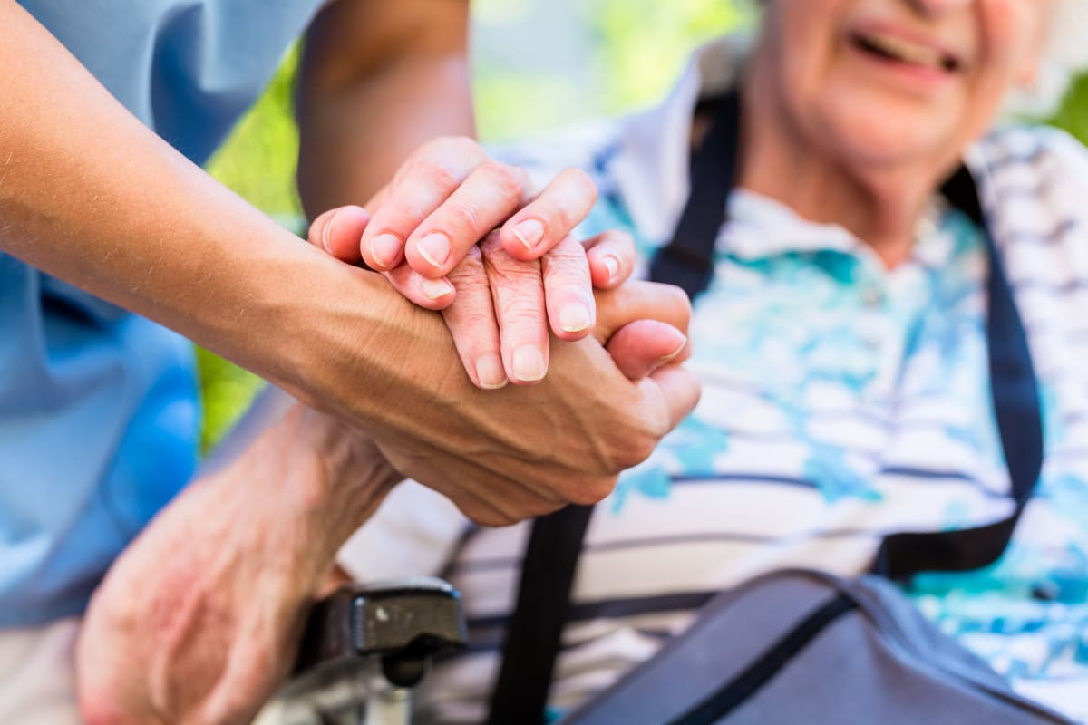 A resident holding hands with a caretaker at Keystone Place at Legacy Ridge in Westminster, Colorado
