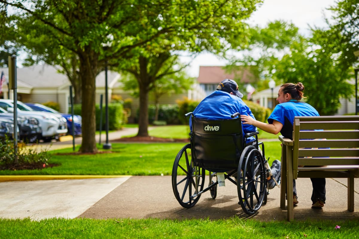 A caregiver with a resident in a wheelchair at Farmington Square Tualatin in Tualatin, Oregon