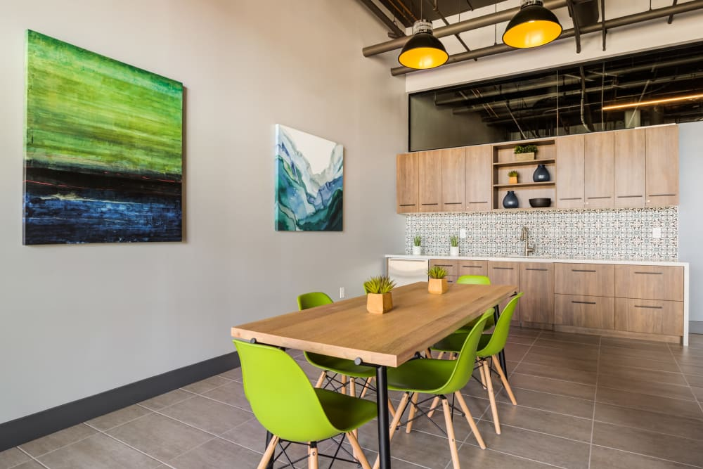 Clubhouse kitchen with dining table and green dining chairs at Lumen Apartments in Everett, Washington