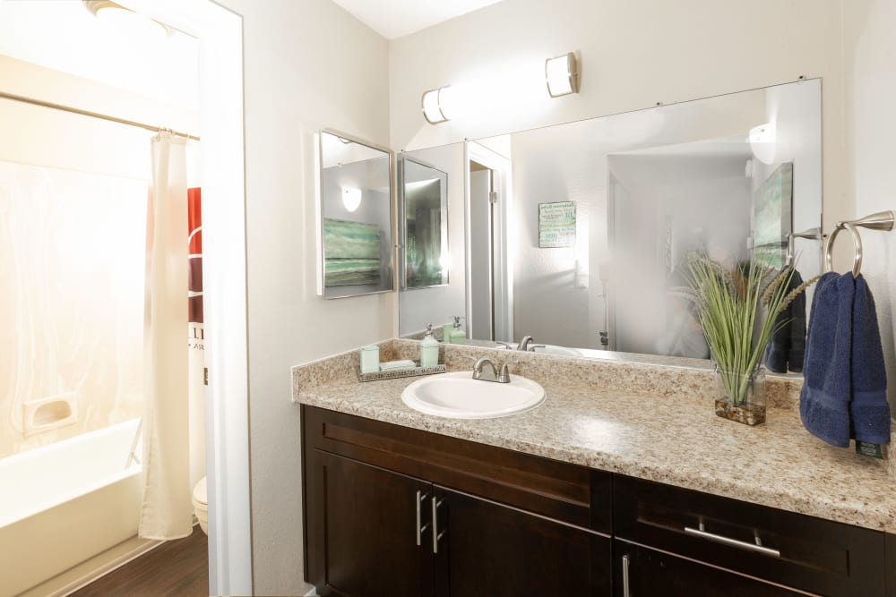 Renovated bathroom with lots of counter space and a large mirror at Callaway Apartments in Taylorsville, Utah