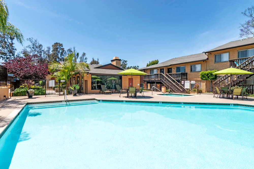 Beautiful resort-style swimming pool with lounge chairs and umbrellas at Hillside Terrace Apartments in Lemon Grove, California