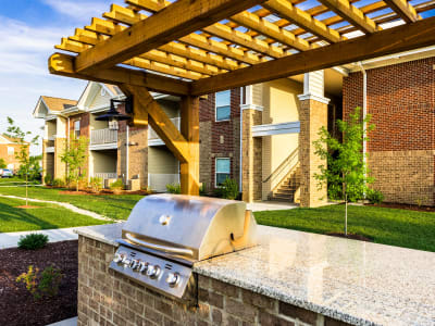 Gas grill with a spacious stone countertop underneath a pergola in the barbecue area at Valley Farms in Louisville, Kentucky