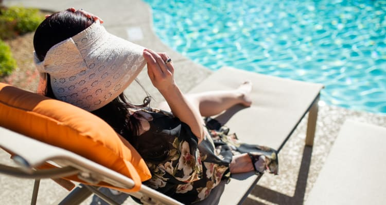 Resident relaxing poolside at Laguna at Arrowhead Ranch in Glendale, Arizona