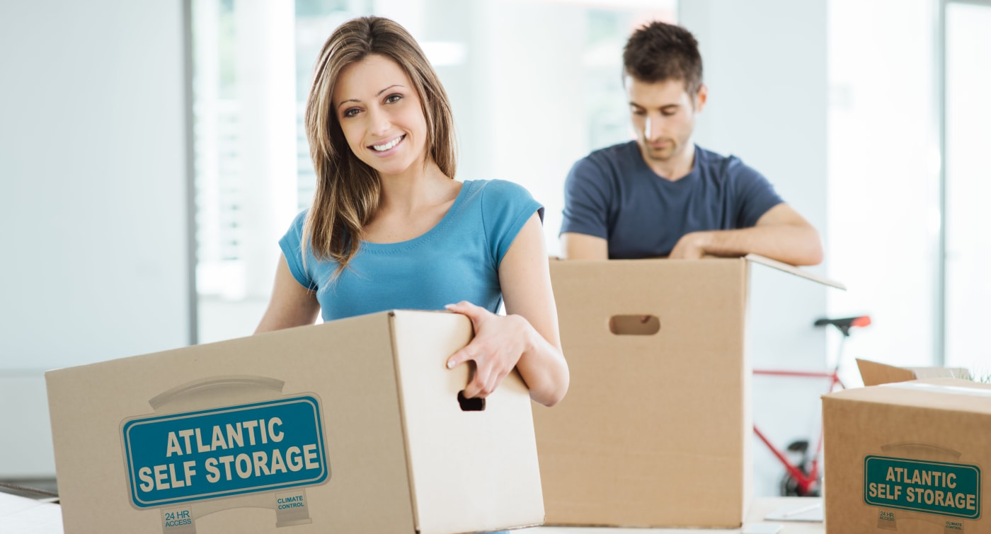 Couple moving into storage unit using boxes from Atlantic Self Storage in Jacksonville, Florida.