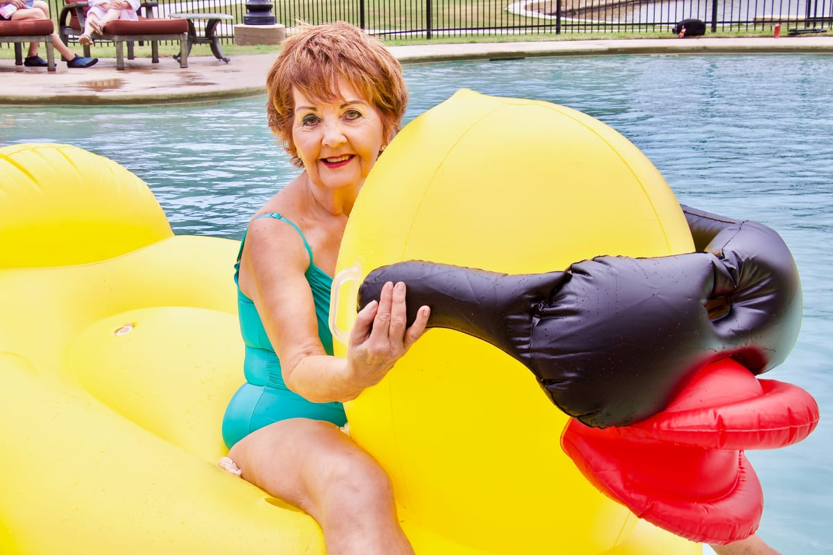A lady on a large inflatable ducky pool toy at Isle at Raider Ranch in Lubbock, Texas