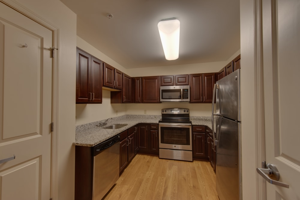 An apartment kitchen with stainless steel appliances at Harmony at Harbour View in Suffolk, Virginia