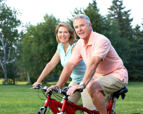 Happy senior couple on bicycles at Stonecrest at Clayton View in Saint Louis, Missouri
