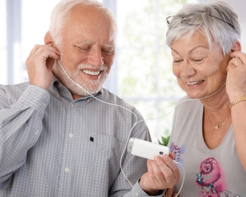 Senior couple listening to music with earbuds at Stonecrest at Clayton View in Saint Louis, Missouri