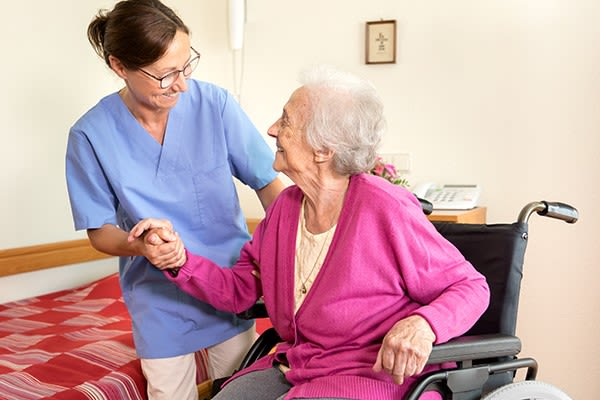 Staff member helping a resident at Heritage Senior Living and their signature programming.