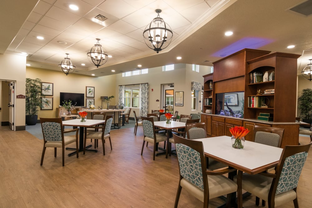Resident dining room with flower centerpieces at CERTUS Premier Memory Care Living in Orange City, Florida.
