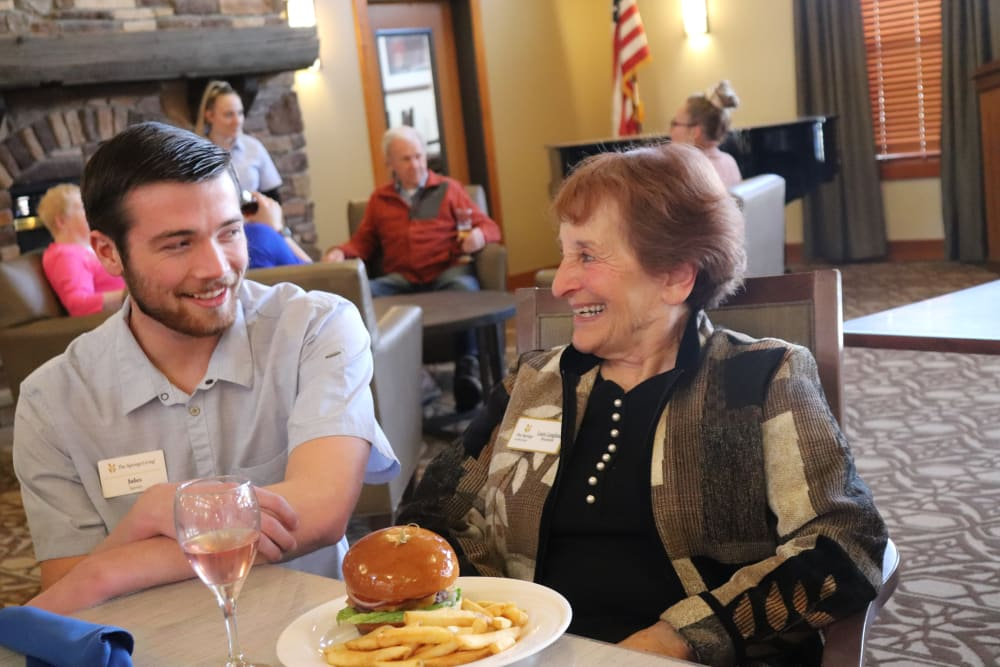 Resident enjoying meal with caregiver at The Springs at Missoula in Missoula, Montana.