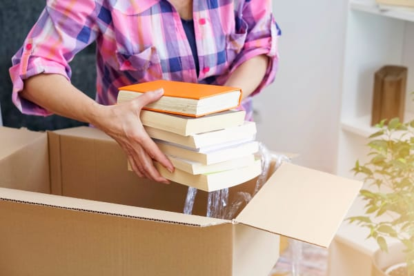 A woman packing boxes at Store It All Self Storage - Kingwood in Kingwood, Texas