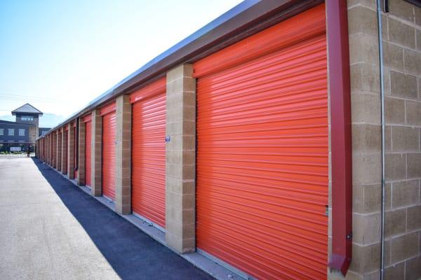 Large, bright orange doors on exterior storage units at STOR-N-LOCK Self Storage in Taylorsville, Utah