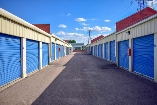 Looking down the middle of two rows of exterior storage units at STOR-N-LOCK Self Storage in Aurora, Colorado