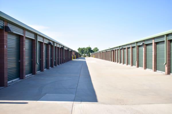 Looking down a wide driveway between exterior storage units at STOR-N-LOCK Self Storage in Fort Collins, Colorado