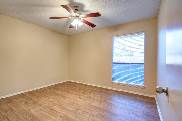 Large windows, hardwood floors, and a ceiling fan in an apartment home's living area at Grayson Ridge in North Richland Hills, Texas