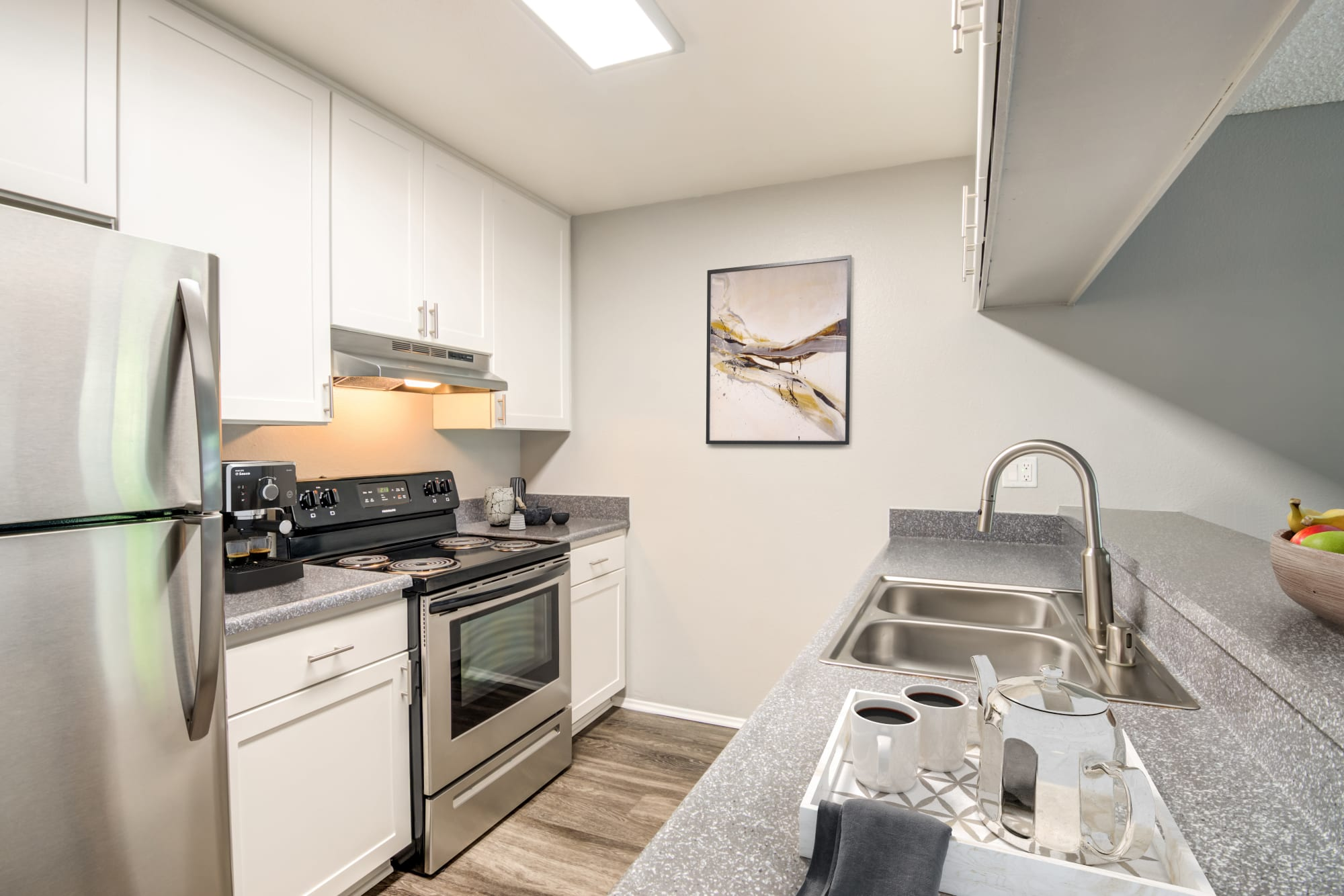 A renovated kitchen with white cabinets at Hillside Terrace Apartments in Lemon Grove, California