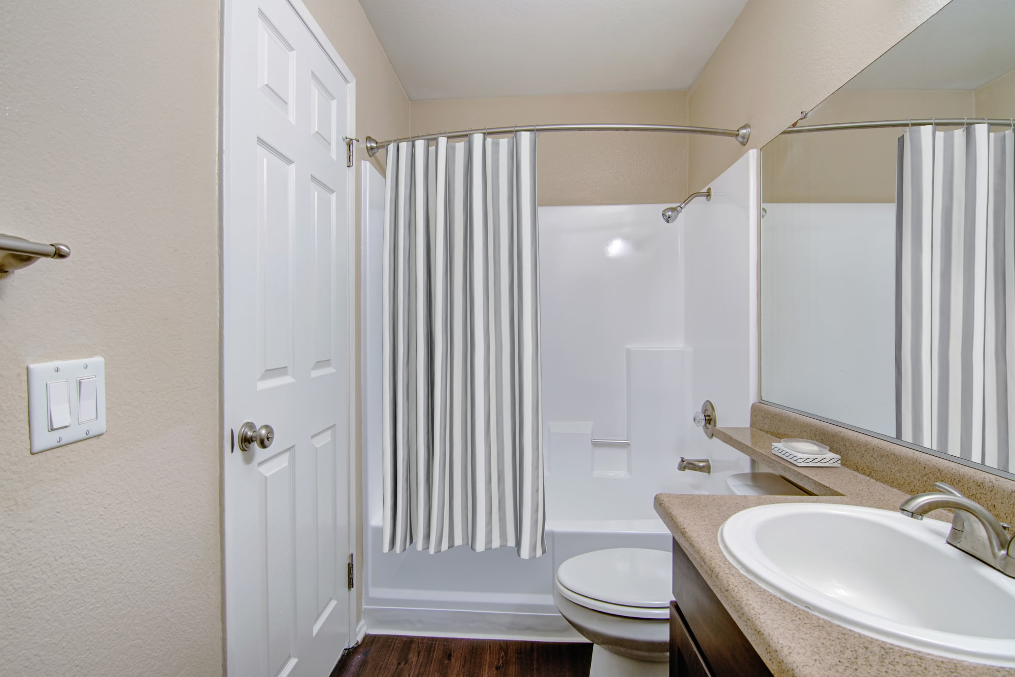 A renovated bathroom with brown cabinets at Hillside Terrace Apartments in Lemon Grove, California