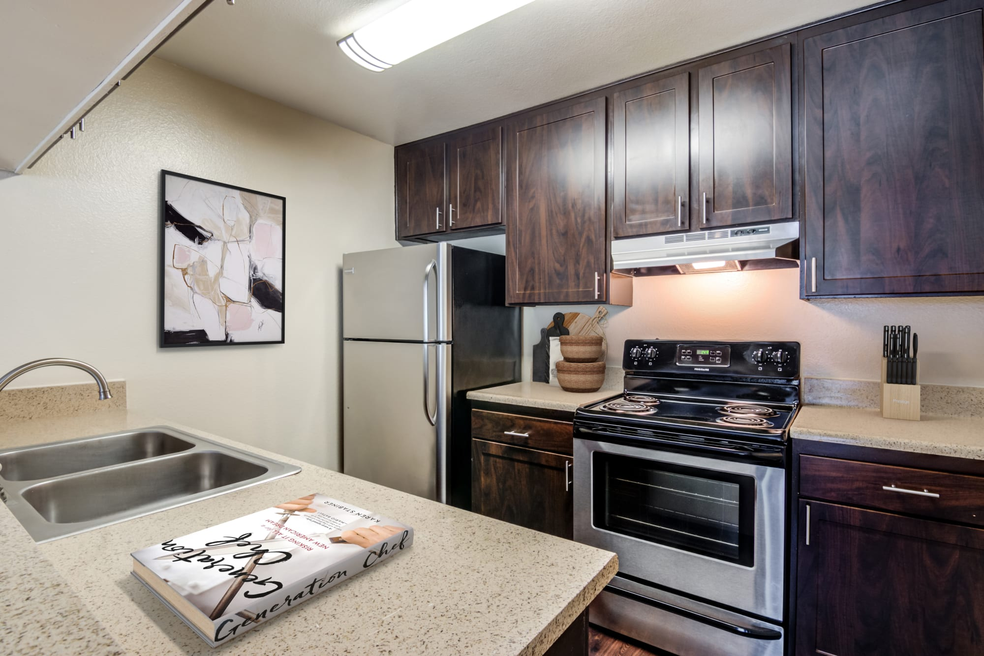 A renovated kitchen with brown cabinets at Hillside Terrace Apartments in Lemon Grove, California