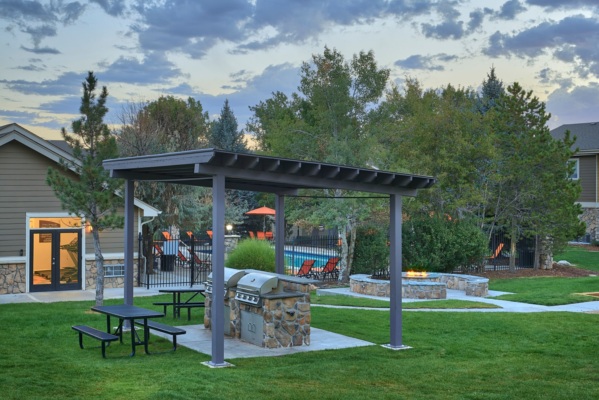 Covered barbecue area at sunset at Crossroads at City Center Apartments in Aurora, Colorado