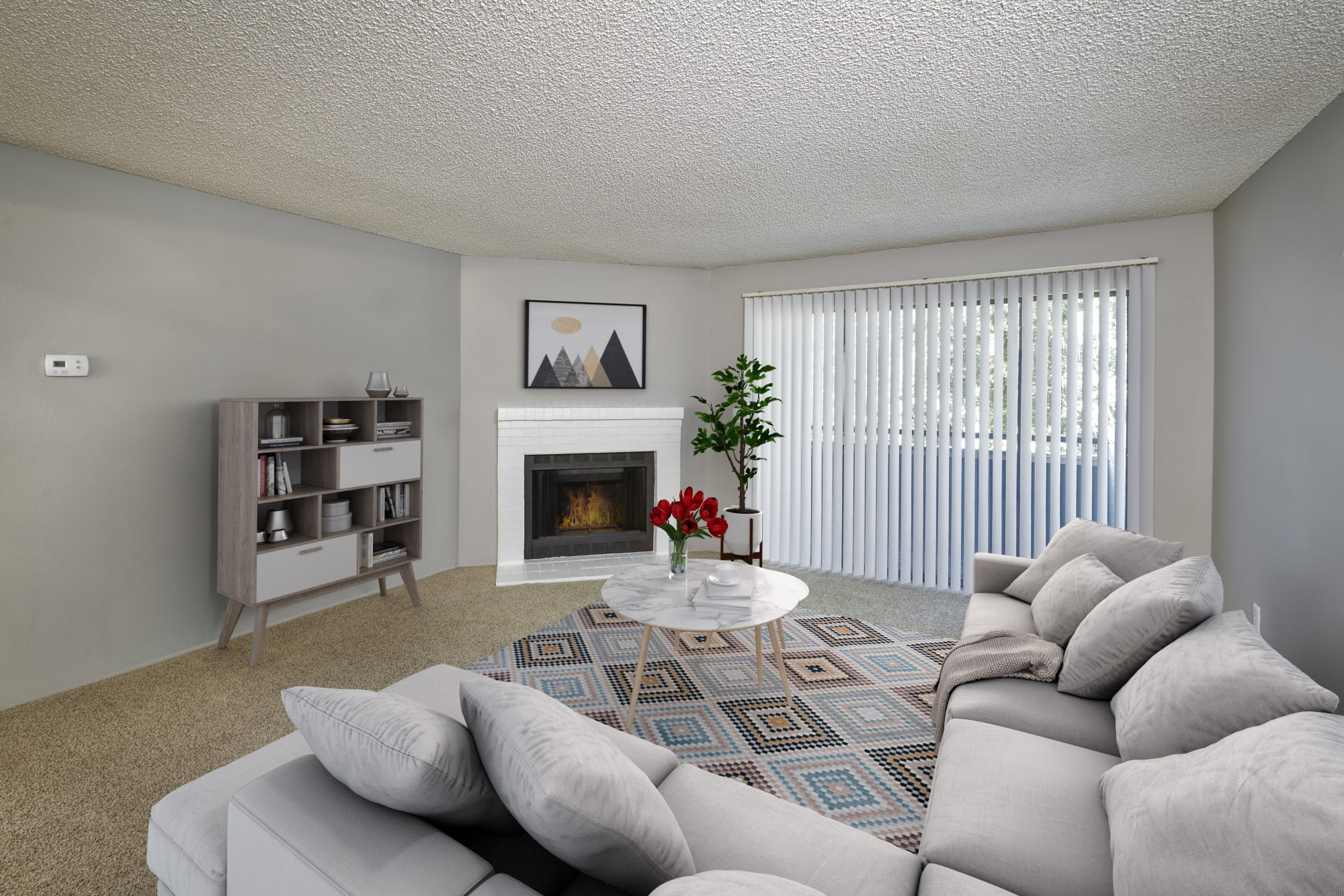 Well decorated living room with a fireplace at Alton Green Apartments in Denver, Colorado
