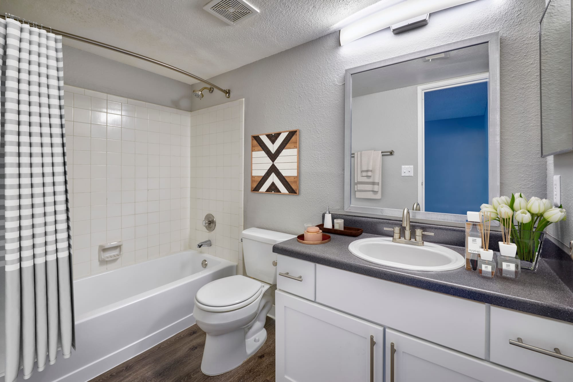A model bathroom with white cabinets at Alton Green Apartments in Denver, Colorado