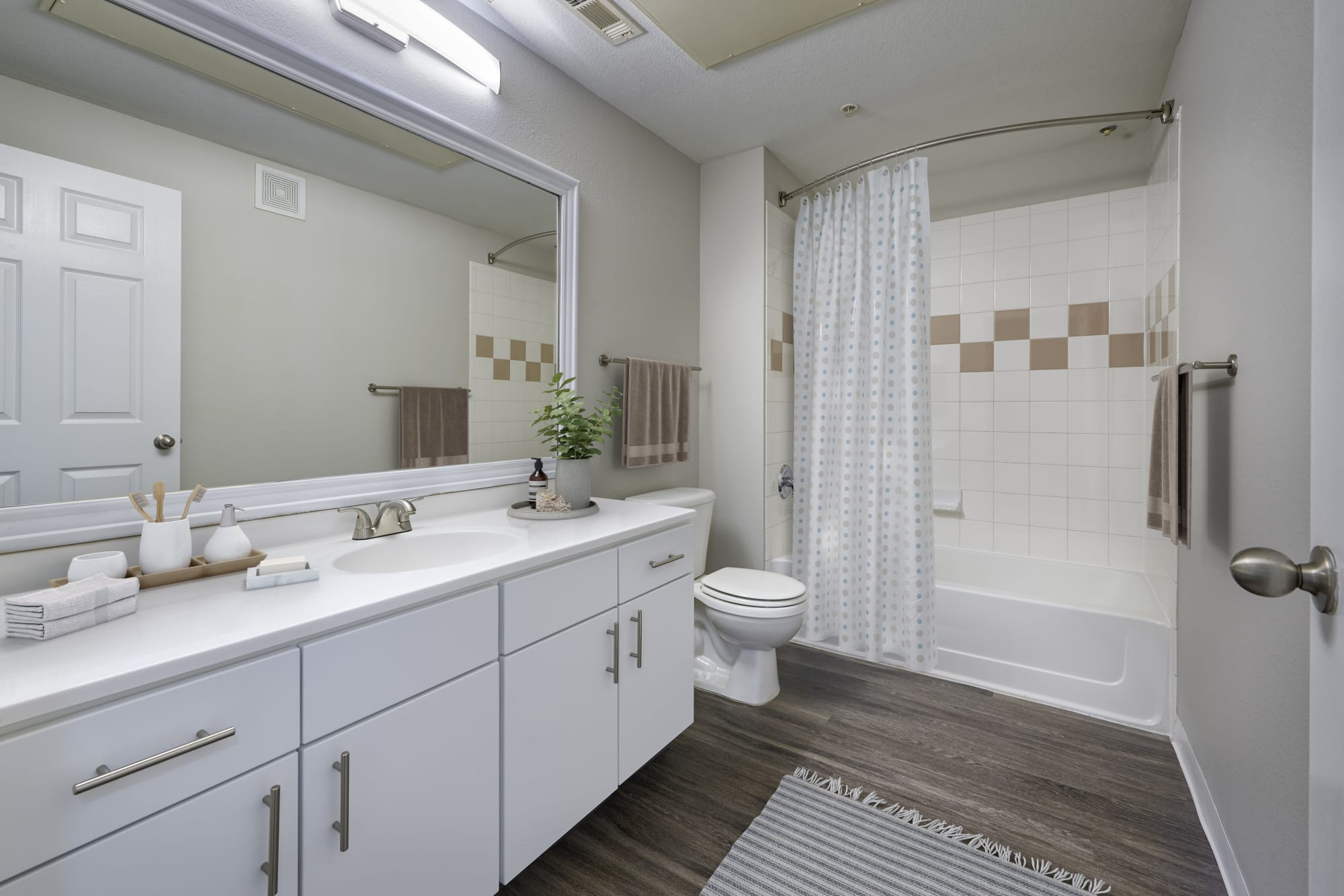 Renovated bathroom with white cabinetry at Bear Valley Park in Denver, Colorado