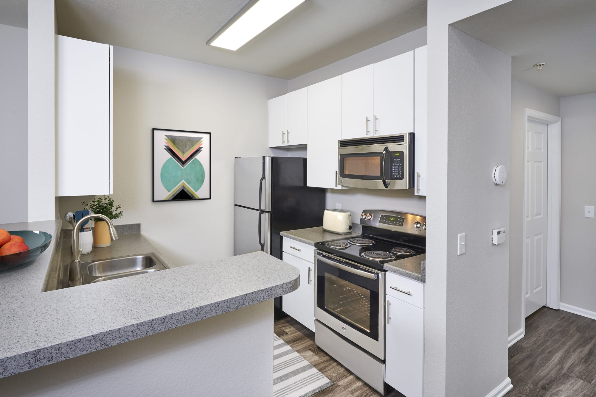 White renovated kitchen with stainless steel appliances at Bear Valley Park in Denver, Colorado