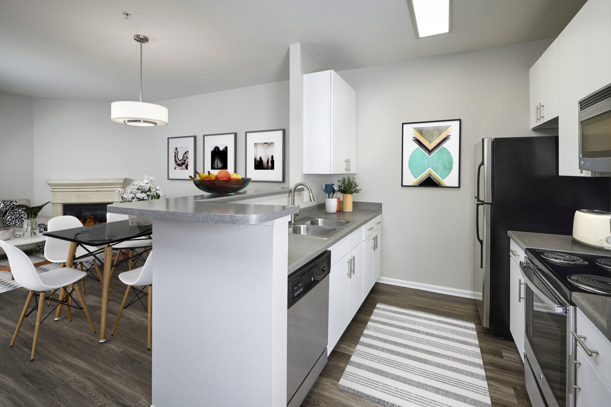 Renovated white kitchen with hardwood floors overlooking the living room with a fireplace at Bear Valley Park in Denver, Colorado