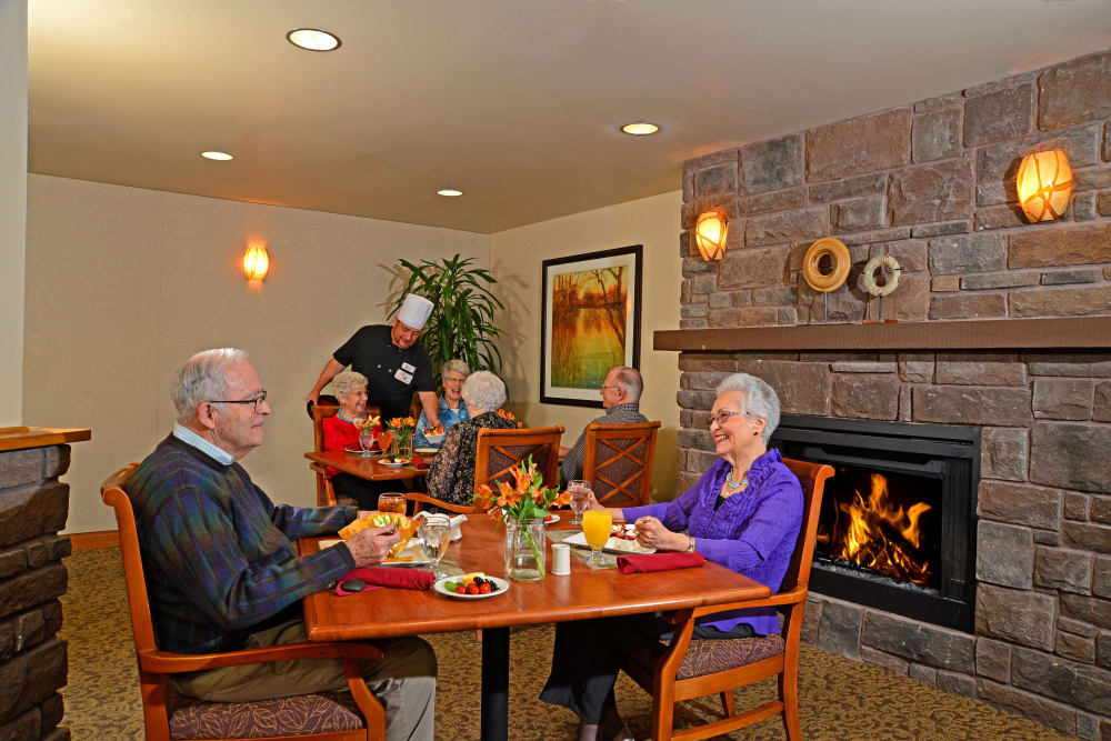 Residents sitting by a fireplace eating at Quail Park of Lynnwood in Lynnwood, Washington