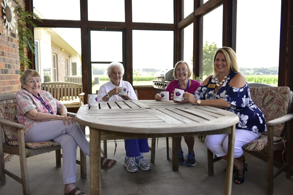 Residents and a staff member enjoying coffee on a porch at Garden Place Columbia in Columbia, Illinois.